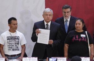 El presidente de México Andrés Manuel López Obrador (c) sostiene el decreto presidencial para la instalación de una Comisión de la Verdad junto a los padres de dos víctimas de los 43 normalistas desaparecidos de Ayotzinapa. FOTO/EFE