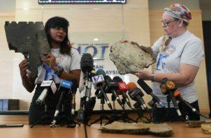 Grace Subathirai Nathan (i), hija de una víctima del vuelo MH370 de Malaysia Airlines, y Jacquita Gonzales, cuyo marido era un miembro de la tripulación, muestran dos piezas que podrían pertenecer al avión que desapareció. EFE