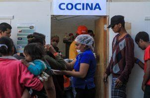 Integrantes de la caravana de migrantes centroamericanos reciben comida en Tijuana. FOTO/EFE