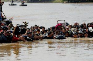 Integrantes de la segunda caravana de migrantes, en su mayoría hondureños, cruzan a pie el río Suchiate. EFE