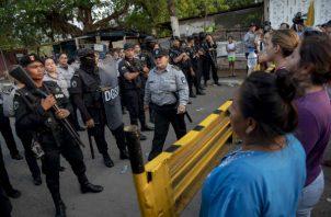 """Antimotines de la Policía Nacional (izq) mantenían un cordón de seguridad frente a familiares de presos de la cárcel """"La Modelo"""". Foto: EFE."""