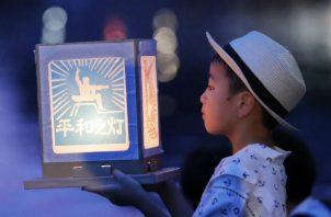 """Un niño sostiene una """"Luz de Paz"""" ante el río Urigami en Nagasaki. Foto: AP."""