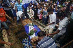 Globos con los colores de la bandera nacional de Nicaragua yacen en la tumba de Matt Andres Romero, de 16 años, quien murió luego de recibir un disparo en el pecho durante la marcha antigubernamental. FOTO/AP