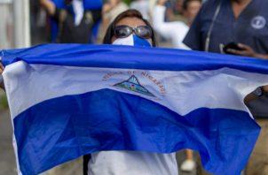 """Un joven con una bandera de Nicaragua participa en una manifestación llamada """"Marcha en Rebeldía"""". FOTO/EFE"""