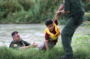 El agente de la Patrulla Fronteriza a cargo del Pase Eagle, Bryan Kemmett, a la izquierda, pasa a un niño de 7 años de Honduras a otro agente luego de que fue rescatado del río Río Grande, cerca del Pase Eagle. FOTO/AP