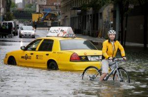 Un ciclista pasa por un taxi varado en una calle inundada de la ciudad de Nueva York cuando la tormenta tropical Irene pasa por la ciudad. FOTO/AP