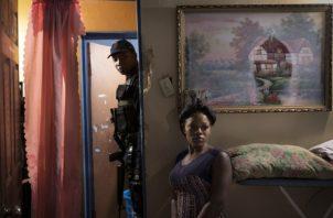 Leyes laxas de armas en EEUU permiten que pistolas de allí hagan estragos en países cercanos. Revisando una casa en Kingston. (Tyler Hicks/The New York Times)