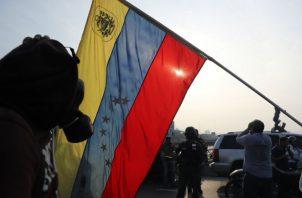 Simpatizantes del presidente interino Juan Guaidó se protegen de las bombas lacrimógenas que las fuerzas de seguridad leales al Gobierno de Nicolás Maduro. Foto/EFE