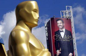 Detalle de estatua de Óscar con el fondo de una imagen del presentador Jimmy Kimmel.  EFE