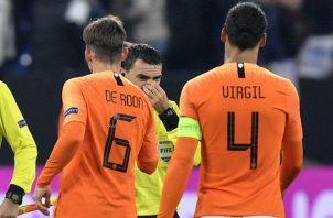 Virgil van Dijk se acerca al ábitro Ovidiu Hategan. Foto AP