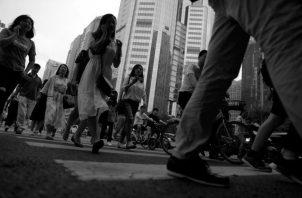 Peatones cruzan la calle en el Distrito Central de Negocios, en Pekín (China). Foto: EFE