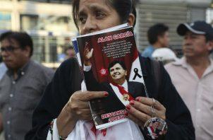Una partidaria de Alan García afligida porta un retrato del expresiente. Foto: AP