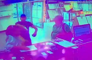 Uno de los delincuentes saca un arma de fuego y apunta directamente a la persona que administraba el local comercial.