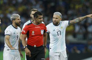 Jugadores argentinos hacen reclamos al árbitro ecuatoriano Roddy Zambrano. Foto AP