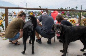 Los residentes locales con sus perros hacen una pausa en un monumento conmemorativo para las víctimas de la embarcación Conception fuera del desembarco marítimo en el puerto de Santa Bárbara. FOTO/AP