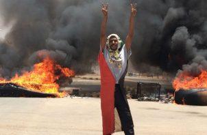 Un manifestante hace la señal de victoria ante neumáticos en llamas en Khartoum, Sudán. Foto: AP.