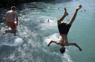 Varias personas saltan al agua desde un puente del río Aar para combatir el calor, este jueves, en Bern (Suiza). La ola de calor que afecta a más de media Europa continúa con temperaturas superiores a las normales. FOTO/EFE