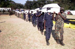 La policía y los oficiales del ejército llevan ataúdes para ser colocados para que los vean sus familiares, en Morogoro,  FOTO/AP
