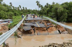 Personal de Protección Civil acordona este lunes el destruido puente que llevaba a la comunidad de Barra Vieja, en el estado de Guerrero (México).