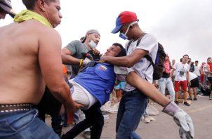 Un hombre herido es ayudado, en Ureña (Venezuela). Dos camiones con ayuda humanitaria solicitada por la oposición fueron quemados por la Policía Nacional Bolivariana en el lado venezolano del puente Francisco de Paula Santander. FOTO/EFE