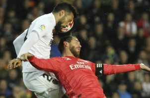 Sergio Ramos del Real Madrid (rojo) disputa un balón ante Ezequiel Garay del Valencia. Foto:AP