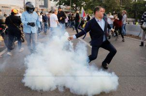 Un oponente del presidente de Venezuela, Nicolás Maduro, devuelve un recipiente de gas lacrimógeno. FOTO/AP