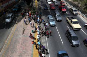 Personas tratan de recoger agua este lunes, en la autopista Francisco Fajardo, en Caracas. FOTO/EFE