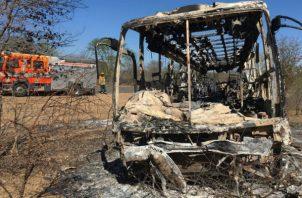 Un camión de bomberos se mantiene estacionado cerca del autobús quemado en Zimbabue. AP