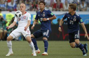 Rafal Kurzawa (izq.) de Polonia  y Hiroki Sakai (cent) de Japón disputan el balón. Foto:AP