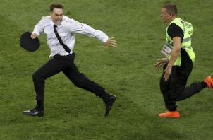 Pyotr Verzilov (Izq.) intenta evadir a un seguridad en la final del mundial de Rusia. Foto:AP