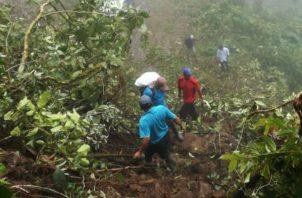 Moradores y docentes arriesgan sus vidas al cruzar en medio del alud de tierra. Foto: Mayra Madrid.
