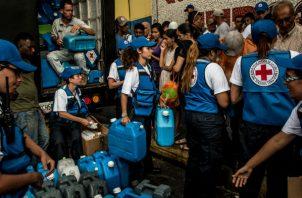 La zozobra en Venezuela ha reducido el acceso de los residentes al agua potable. La Cruz Roja ayuda en Caracas. Foto/ Meridith Kohut para The New York Times.