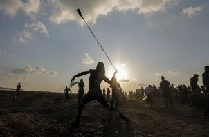 Un  israelí observa su vehículo impactado por misiles tirados desde la Franja de Gaza. Foto: AP.