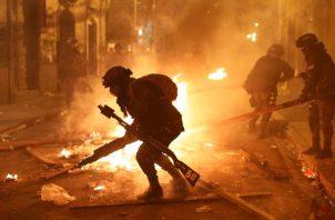 La policía desmantela una barricada en llamas durante una protesta contra la reelección del presidente Evo Morales, en La Paz, Bolivia. FOTO/AP