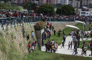 Personas suben por las paredes para salir de un concierto en las instalaciones del Parque Generalisimo Francisco de Miranda este sábado en Caracas. FOTO/EFE