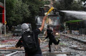 Un manifestante antigubernamental arroja una botella llena de pintura contra un cañón de agua de la policía que avanza durante los enfrentamientos en Santiago. FOTO/AP