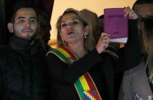 La segunda vicepresidenta del Senado de Bolivia y opositora Jeanine Ánez, en el centro, con la faja presidencial y sosteniendo una Biblia, se dirige a la multitud desde el balcón del palacio de Quemado después de que ella se declarara presidenta. FOTO/AP