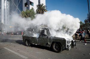 Choque entre Carabineros y manifestantes en medio de los gases lacrimógenos. FOTO/EFE