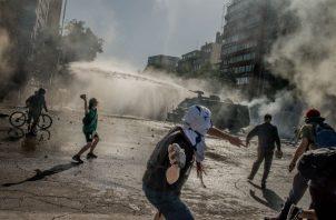 La clase media chilena lucha con precios altos y sueldos bajos. Un reciente choque con la Policía en Santiago. Foto/ Tomas Munita para The New York Times.