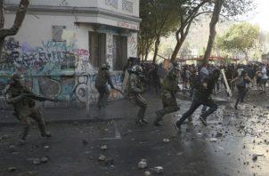 Manifestante chileno frente a policías antidisturbios en Santiago. Foto: AP.