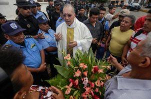 El padre Edwin Roman intenta convencer a la policía de que permita que parientes de manifestantes antigubernamentales encarcelados y muertos ingresen a la Iglesia de San Miguel Arcángel en Masaya. FOTO/AP