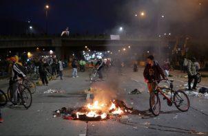 Manifestantes le gritan consignas a los agentes policiales. FOTO/AP