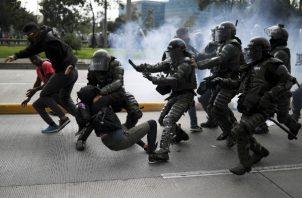 Miembros del orden público tratan de atrapar a unos manifestantes durante el paro nacional en Colombia. FOTO/AP
