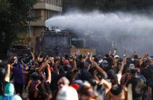 """Manifestantes y carabineros se enfrentan en la Plaza Italia, rebautizada popularmente como """"Plaza de la Dignidad"""", durante una jornada marcada por las movilizaciones en contra del sistema privado de pensiones, en Santiago. FOTO/EFE"""