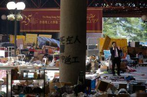 Un hombre está rodeado de basura después de las principales protestas en el campus de la Universidad Politécnica de Hong Kong. FOTO/AP