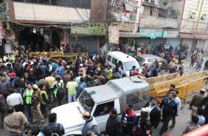 La policía y los periodistas indios se encuentran cerca del sitio donde estalló un incendio en Nueva Delhi. FOTO/AP