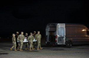 Un equipo de transporte de la Fuerza Aérea mueve una caja de transferencia que contiene los restos del marinero de la Armada Mohammed Sameh Haitham, de San Petersburgo, Florida, el domingo 8 de diciembre de 2019, en la Base Dover de la Fuerza Aérea, Del. FOTO/AP