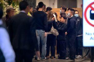 Los dolientes se alinean para presentar sus respetos a Chow Tsz-lok, un estudiante que murió en un estacionamiento durante una protesta en noviembre. FOTO/AP