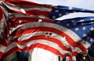 Un manifestante rompe una bandera estadounidense durante una protesta multitudinaria contra Estados Unidos, este viernes en Teherán. Foto EFE