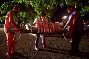 Los voluntarios distribuyen alimentos a los vecinos que permanecen al aire libre por miedo a nuevas réplicas. FOTO/AP